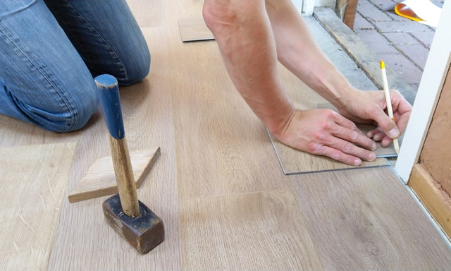 man measuring floor tiles