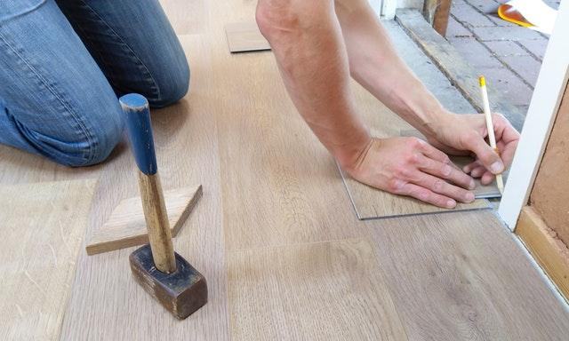 man measuring floor tiles